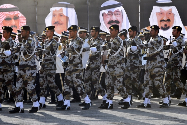 Saudi soldiers march past posters of royal family (AFP).jpg