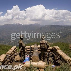Soldiers stand guard on top of a mountain